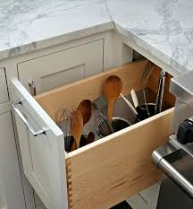 Beside a stainless steel stove, a white shaker cabinet finished with a  polished nickel pull pulls out to reveal a utensils drawer fitted with  three built in ...