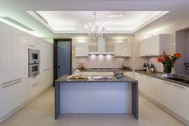 modern white kitchen with grey counter and chandelier