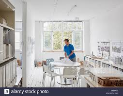 modern office plans. A Modern Office. Man Looking At Plans Table, Architectural Drawings. Office