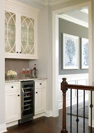 kitchen bar features ivory cabinets adorned with oil rubbed bronze s ed with gl door wine cooler topped with gray granite countertops and paired