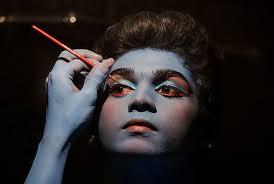 an artist applying make up for an indian clical dance