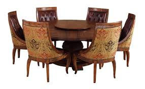 antique and vintage expandable round pedestal dining table with old decoration and 6 brown leather tufted dining chairs with wooden frame and back fabric