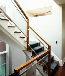 Walnut wood railing. Matte aluminum edging on the glass creates a finished  look. Builder