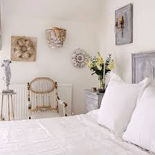 Cool white bedroom with wall art, white cotton bedsheets, grey bedside  table and white