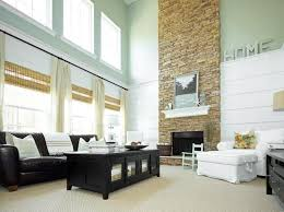 light living room with tall stacked stone fireplace