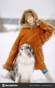 smiling cute little girl in a fur coat baby red color is winter in the snow for dog raising one hand outdoors photo by andreipugach