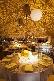 lighting ideas for weddings. gobo lights project yellow foliage along the cieling of this outdoor wedding tent while paper lanterns hover over reception tables lighting ideas for weddings l