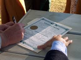 michigan weddings dr stephan j smith \u2022 wedding officiant Wedding License Genesee County Mi close up photo of a marriage license being signed outdoors by a newly wedded couple marriage license genesee county mi