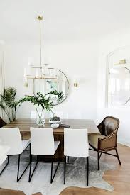 dining table with cowhide rug and wood table with gold chandelier