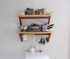floating brown wooden kitchen shelves for bottles and pans placed on the white