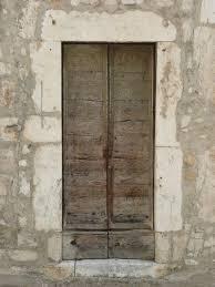 worn uneven wood door with no casing and no handle
