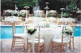 pool backyard wedding decorations mixed with goldenrod wooden chairs and flower bouquets also round table under large white table cloth facing clear water