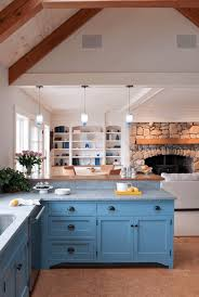 rustic blue kitchen cabinet with stone wall and fireplace