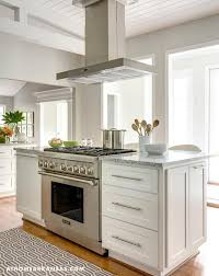 stove island. a stainless steel kitchen hood stands over island fitted with white cabinets and stove