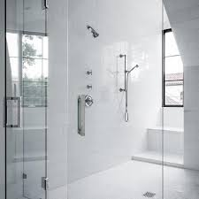 spacious walk in shower boasts walls clad in large white subway tiles lined with a polished nickel modern shower kits