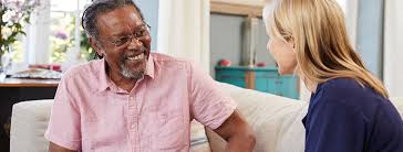 older client sits on a sofa having a discussion with his social worker