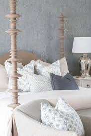 sat against gray wallpapered walls a noir ferret weathered bed dressed in cream bedding accented with a blue and cream accent pillows is sat beside a white