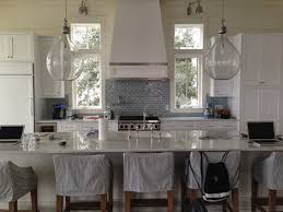 restoration hardware counter stool in white and grey kitchen with wooden chairs big lamps and square