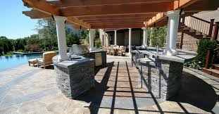 wonderful outdoor kitchens design ideas with stone material countertops and wooden lounge chairs feat awesome swimming pool view