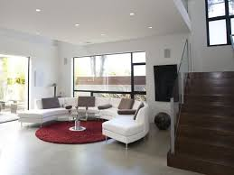 area rug for living room mixed with curved white sofa and dark brown stairs plus large glass windows