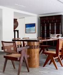 barnes placed pierre jeanneret chairs around an antique indonesian table in the dining room of the