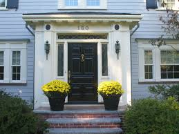 beautiful flowers on standing vase enhancing fabulous front entry doors that painted in black