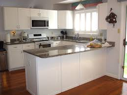 painting oak kitchen cabinets with white chalk paint color plus microwave shelf under mounted cabinet and marble countertop plus brown hardwood floor tiles