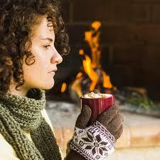 Donna che gode della bevanda calda vicino al camino | Foto Gratis
