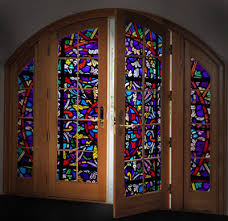 colorful stained glass panels in a large wooden door make it a beautiful way to greet