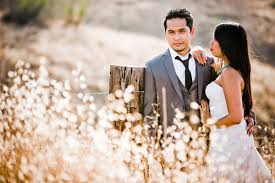 bride and groom standing next to barbed wire fence in the countryside bride is wearing white dress with turquoise jewelry