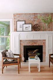 toned down brick fireplace surround extends up the wall with white molding and mantle