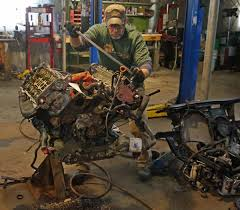 mechanic bill smith works on a car engine in the he and andy wellman are