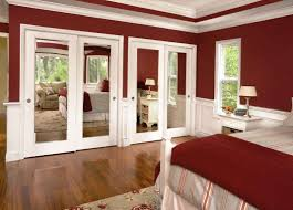 mirrored bifold closet doors in bedroom with red white wall and wooden ceramics tile