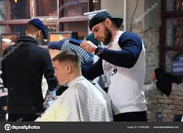 Young Guys Making Haircuts In The Hipster Style Barber Shop In Kiev