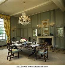 antique crystal chandelier above antique table and chairs in green panelled country dining room with cream carpet