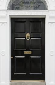 this stately black door features deep panels and br details including lock cylinder mail