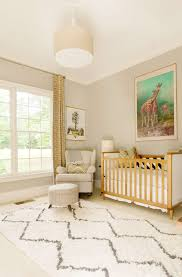 a neutral modern nursery is adorned with patterned throw pillows a small footstool