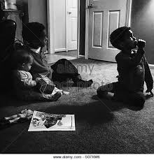black kids watching tv. two men and a baby - stock image black kids watching tv i