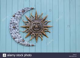 sun and crescent moon decorative garden wall art on blue timber cottage dorset england on sun moon garden wall art with metal garden ornament sun moon stock photos metal garden ornament