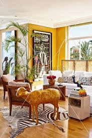 corner of yellow painted living room with lounge area and shiny gold sheep sculpture on