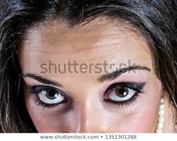 beautiful big brown eyes with beautiful makeup look up into the camera close up