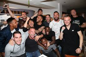 Settle down boys: Players on the champion Leicester City Football Club  watch rivals on TV