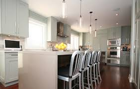 modern pendant lighting kitchen. natty wooden cabinets and kitchen table with four chairs illuminated by modern pendant lighting fixtures at expansive room display g
