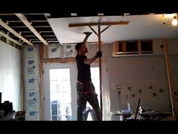 how to hang sheet rock that is how it is done sheetrock to ceiling with two hands and a