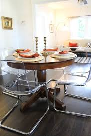 Clear Acrylic Dining Chairs Paired with Traditional Pedestal Table eclectic- dining-room