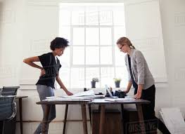 office furniture women. Two Women Stand Working At Opposite Sides Of An Office Desk Furniture N