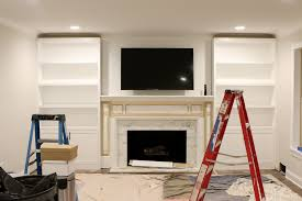 the step by step process of installing whte built ins around a fireplace