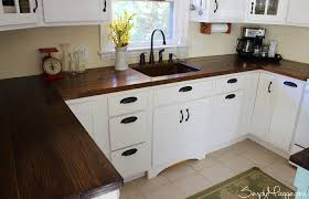 white cabinets and island in small kitchen dark wooden countertop