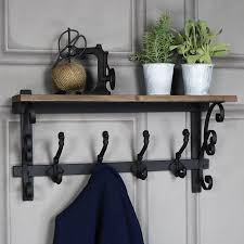 ornate wooden wall shelf with coat hooks
