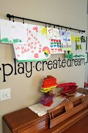 cute way to display children's artwork - curtain rod, hooks, and wall word  decals saying play, create, and dream. Kids room and play room